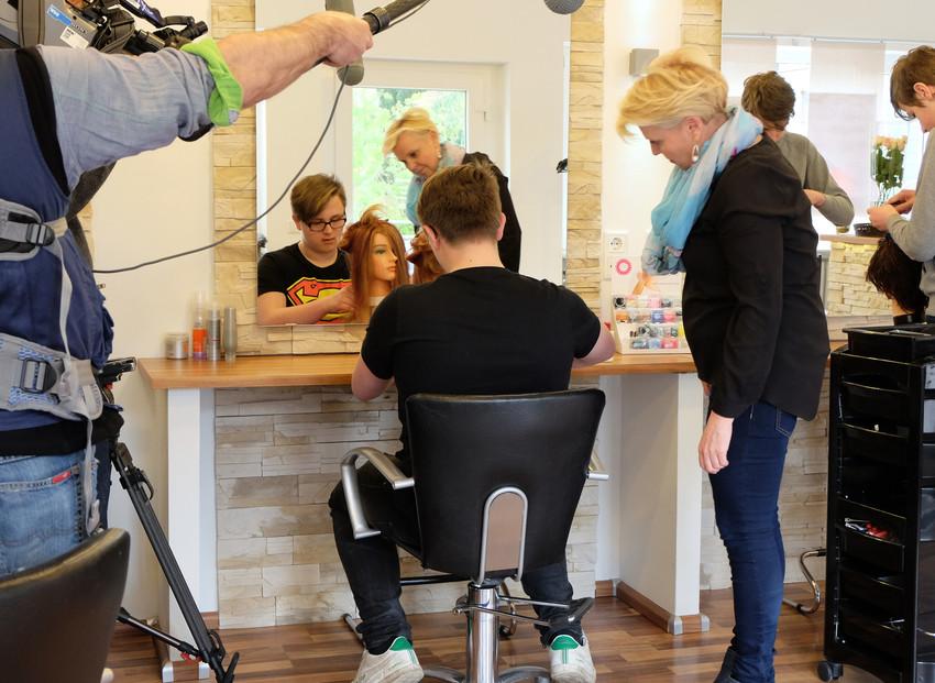 Junge frisiert Perrücke, Friseurin und TV-Team sehen zu