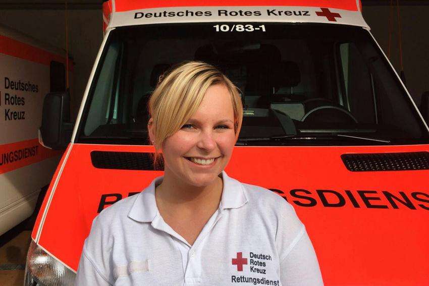Frau vor einem Rettungswagen